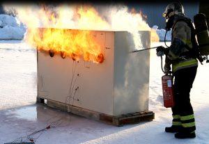 Pelastajan asusteisiin pukeutunut henkilö suorittaa polttokoetta, sammuttaa käsisammuttimella pientä paloa.